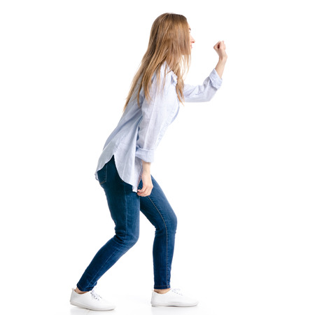 Woman in jeans and blue shirt knocking on the door isolated on white background