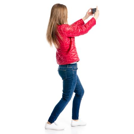Hermosa mujer en chaqueta roja y jeans en mano smartphone selfie aislado sobre fondo blanco, vista posterior