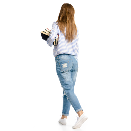 Woman in blue jeans and shirt with books in hands goes isolated on a white background, back view