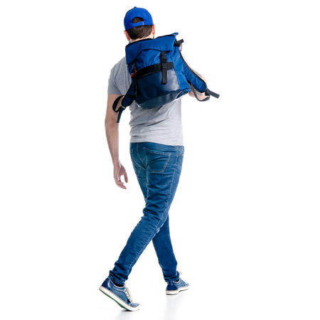 A man tourist in jeans and cap, blue backpack goes walking on white background isolation, back view