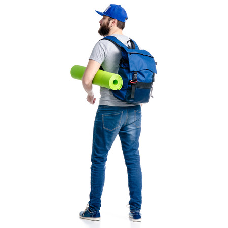 A man tourist in jeans and cap, blue backpack karemat standing looking on white background isolation, back view