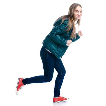 Woman in jeans and jacket running isolated on a white background. Foto de archivo