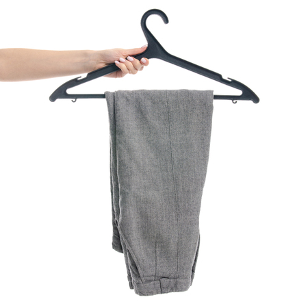 Gray pants on a hanger in hand. Isolated on a white background.