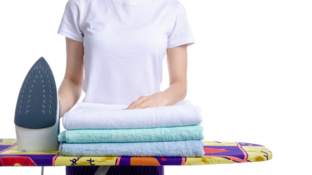 Woman ironing laundry towels on iron board on white background isolation