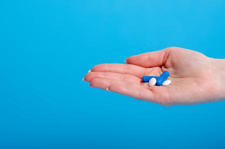 Pills in hand pharmasy medecine on blue background