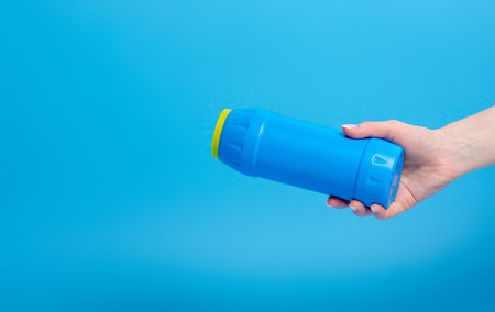 Blue bottle detergent powder in hand on blue background