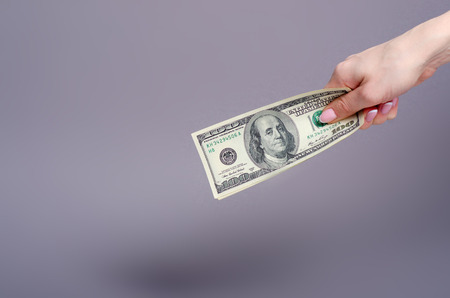 Dollars money finance currency in hand on gray background