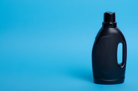 Black bottle laundry gel on blue background isolation