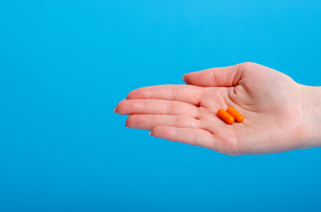 Orange pills capsule in hand pharmasy medecine on blue background Stock Photo