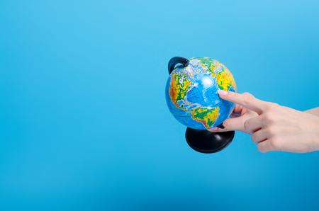 Globe world in hand on blue background