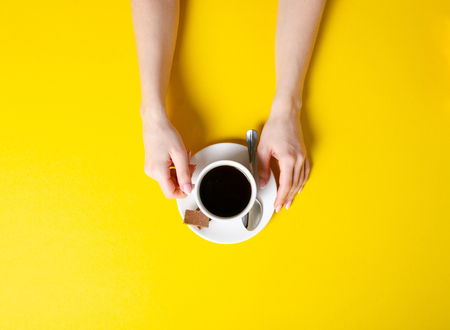 Cup of coffee with chocolate pieces in hand on yellow background, top view