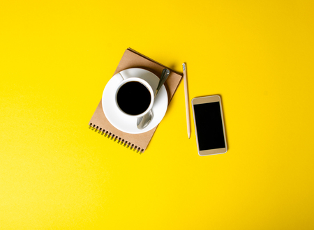 Cup of coffee, notepad, pencil, mobile phone on yellow background, top view