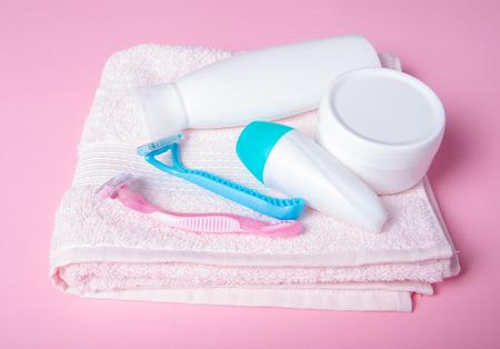 Pink towel, jar cream, lotion, razor, roller deodorant soft beauty on pink background