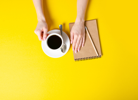 Cup of coffee, notepad, pencil, female hands on yellow background, top view