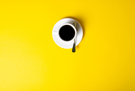 Cup of coffee drink on yellow background, top view
