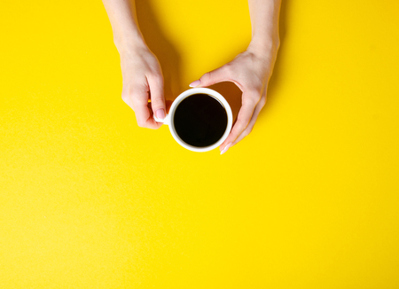 Cup of coffee in hand on yellow background Imagens