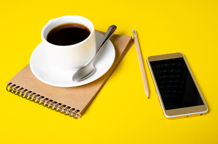 Cup of coffee, notepad, pencil, mobile phone on yellow background
