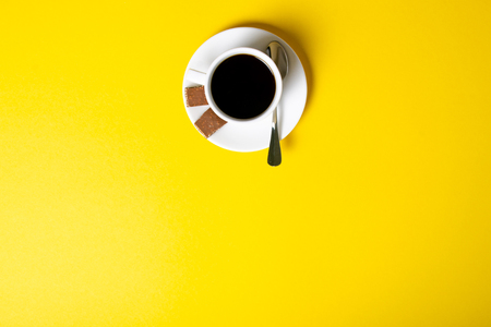 Cup of coffee with chocolate pieces on yellow background, top view Stock Photo - 117888730