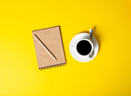 Cup of coffee, notepad, pencil on yellow background, top view Stock Photo - 117888737