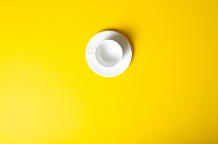 Empty cup with saucer on yellow background, top view