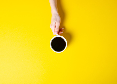 Cup of coffee in hand on yellow background, top view Foto de archivo