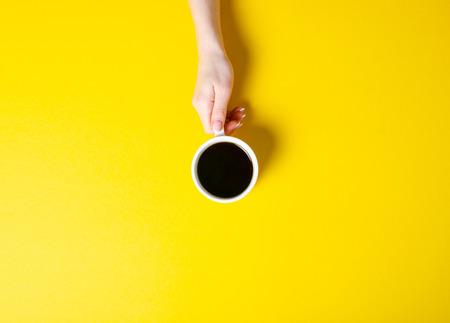 Tasse Kaffee in der Hand auf gelbem Hintergrund, Ansicht von oben