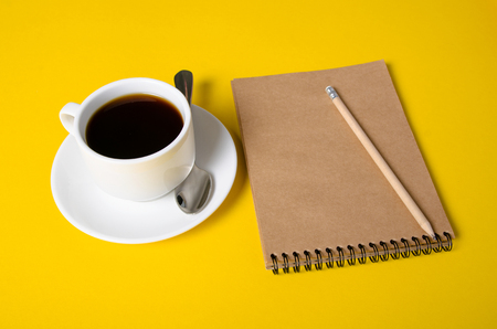 Cup of coffee, notepad, pencil on yellow background Imagens
