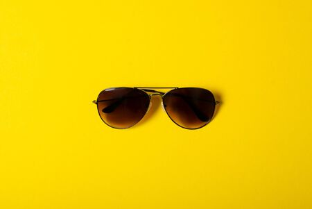 Sunglasses fashion style on yellow background, top view