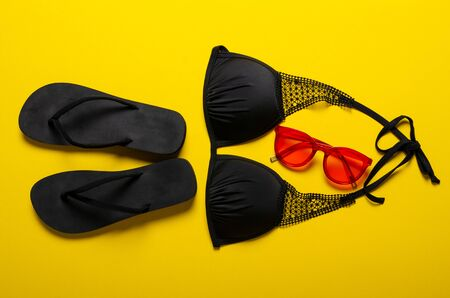 Swimsuit, sunglasses and flip flops on yellow background, top view Standard-Bild - 143136904