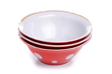 Old red polka dot plates on a white background. Isolation