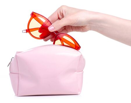 Red sunglasses put in pink cosmetic bag