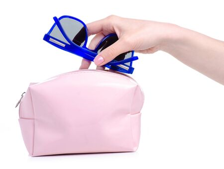 Blue sunglasses put in pink cosmetic bag
