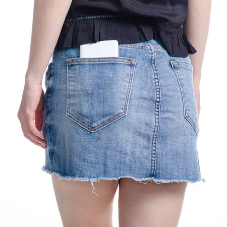 Woman puts mobile phone in jeans skirt pocket