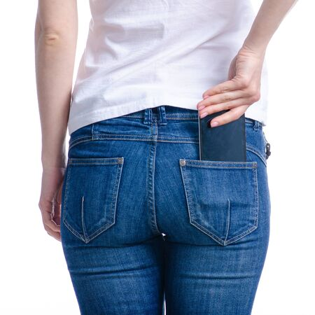 Woman puts mobile phone in jeans pocket