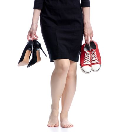 Woman legs choice high heels or sneakers on white background isolation