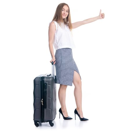Woman in high heels shoes and skirt with travel suitcase standing smiling