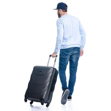 旅行スーツケースを持つジーンズの男が歩いて行く
