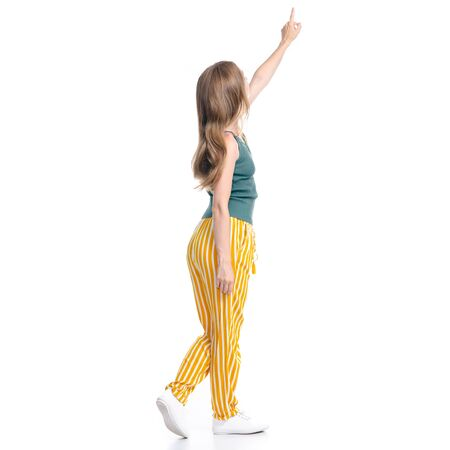 Woman in yellow pants smiling happiness standing looking showing pointing on white background isolation, back view Standard-Bild