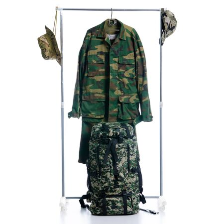 Camouflage military clothing and backpack on hanger rack Stock Photo