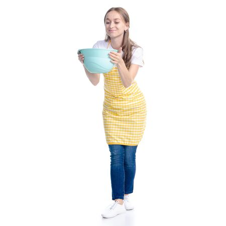 Woman in yellow apron with kitchen bowl in hand Standard-Bild