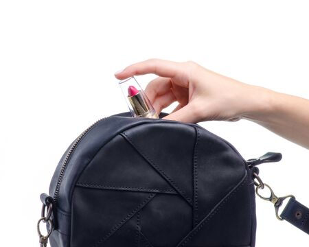 Female hand put lipstick in black round bag on white background isolation Banque d'images