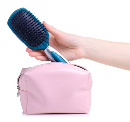 Blue hair brush put into pink cosmetic bag on white background isolation Archivio Fotografico