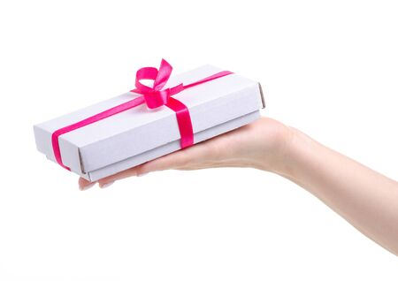 White box with pink ribbon bow gift in hand