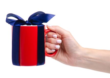Red cup mug with blue ribbon bow gift in hand Standard-Bild