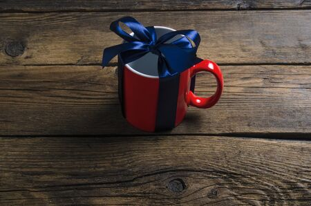 Red cup mug with blue ribbon bow gift Standard-Bild