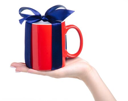 Red cup mug with blue ribbon bow gift in hand 写真素材