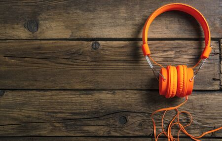 Orange headphones music audio on wooden background