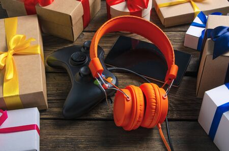 Orange headphones music audio, gamepad, smartphone, mobile phone, box with ribbon bow gift