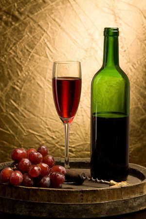 Glass of red wine and bottle on a background oak flanks and grapes photo