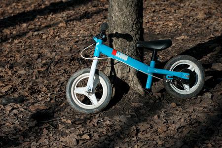 fondo para bebe: azul balance bicicleta runbike sin pedales para niños en el parque de fondo marrón Foto de archivo
